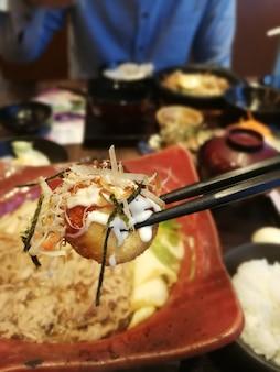 Close de takoyaki, bola de takoyaki presa no chopstick