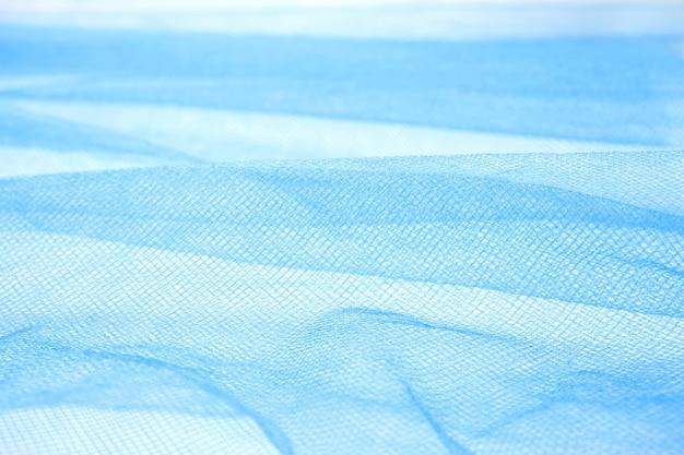 Close de tecido de organza azul ondulado, fundo abstrato e textura