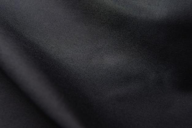 Close de tecido de seda preto ondulado, fundo de textura de tecido preto