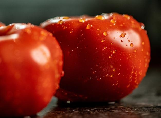 Close de tomates frescos maduros com gotas de água em uma bancada de cozinha de granito preto