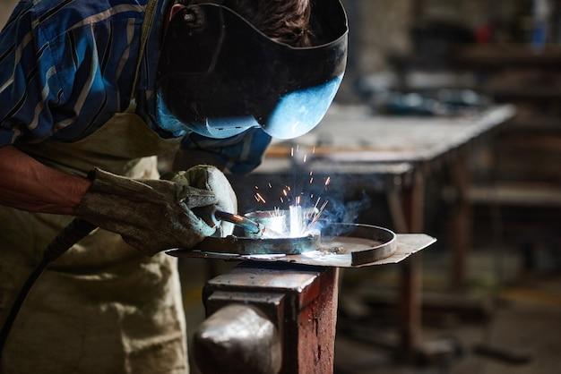 Close de trabalhador com máscara protetora usando solda para trabalhar com metal na fábrica