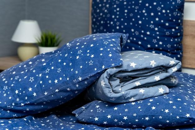Close de travesseiros e cobertores azuis com um lençol na cama dentro de casa