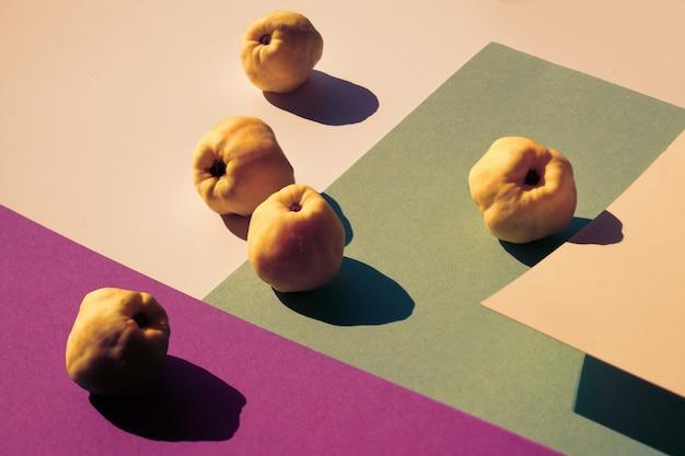 Close de três frutos de marmelo japonês em papel de camadas geométricas rosa e roxo