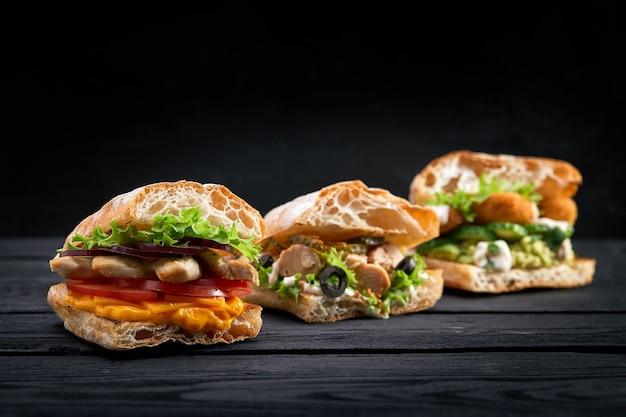 Close de três hambúrgueres de sanduíches apetitosos diferentes em fundo preto de madeira