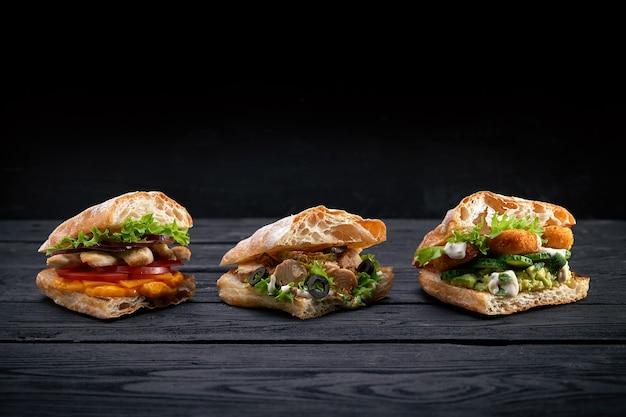 Close de três hambúrgueres de sanduíches apetitosos diferentes em uma superfície de madeira preta