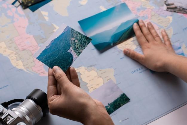 Close de turista vendo fotos de viagens e colocando no mapa de papel
