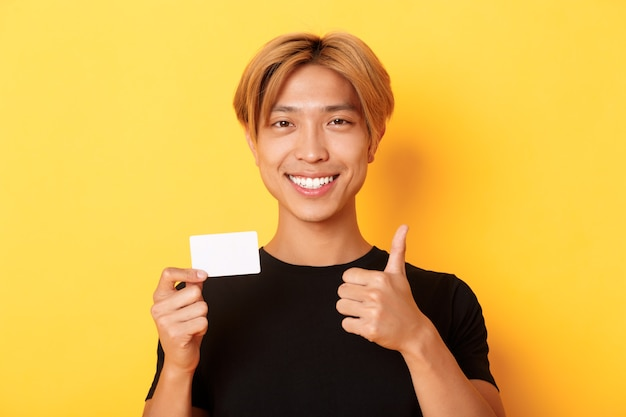 Close de um asiático satisfeito recomendado banco, mostrando o cartão de crédito e em pé sobre a parede amarela