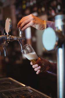 Close de um bar tenro enchendo a cerveja da bomba do bar
