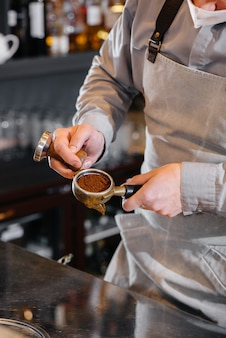 Close de um barista mascarado preparando um delicioso café no bar de um café o trabalho de restaurantes e cafés durante a pandemia