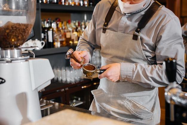 Close de um barista mascarado preparando um delicioso café no bar de uma cafeteria