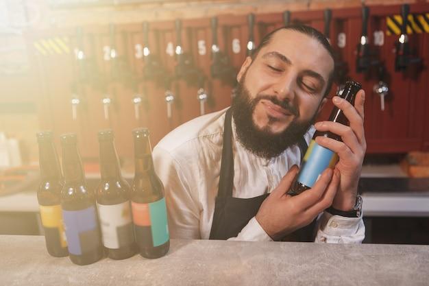 Close de um barman abraçando uma garrafa de cerveja