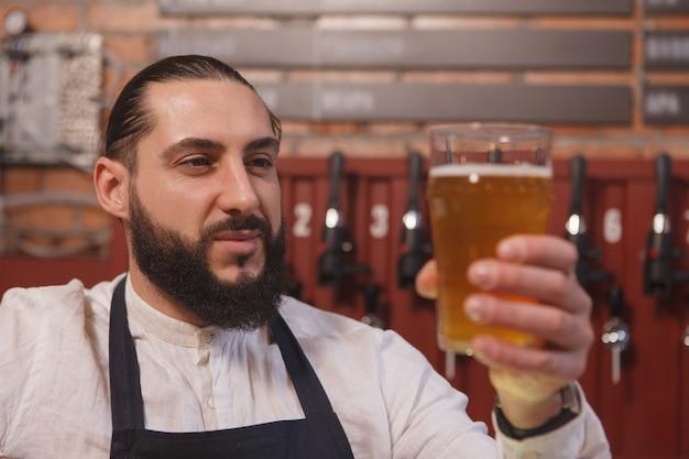 Close de um barman alegre sorrindo alegremente, examinando a cerveja no copo