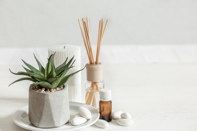 Close de um bastão de aroma para o cheiro de um ambiente e um pote de óleo aromático.