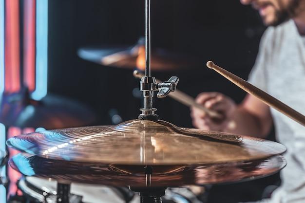 Close de um baterista tocando um prato de bateria, parte de uma bateria em uma tomada cortada.