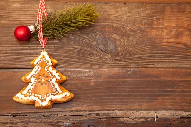 Close de um biscoito em forma de árvore de natal com uma pequena decoração em um fundo marrom