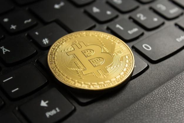 Close de um bitcoin colocado em um teclado preto de computador