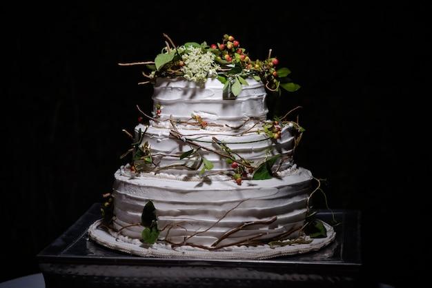Close de um bolo de casamento rústico com folhas verdes, galhos e pequenas frutas redondas