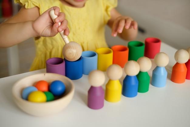 Close de um brinquedo classificador com copos de bolas e uma colher de pau