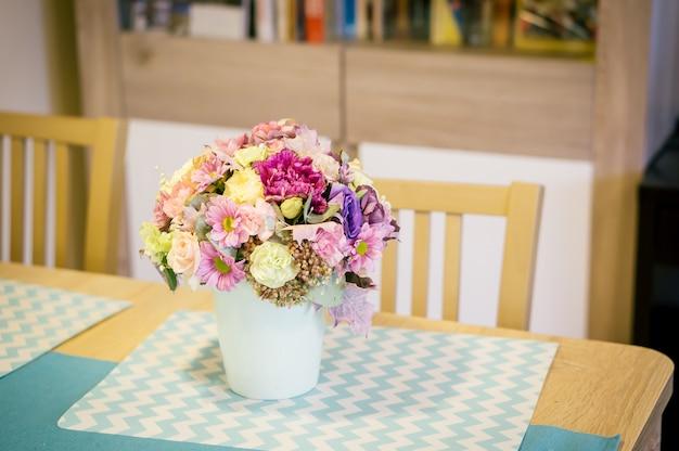 Close de um buquê de flores coloridas em um vaso branco sobre uma mesa de madeira