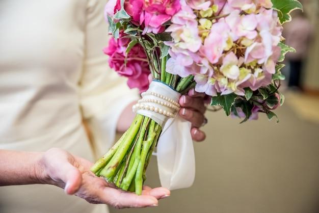 Close de um buquê de flores de noiva feito de várias flores em tons de rosa