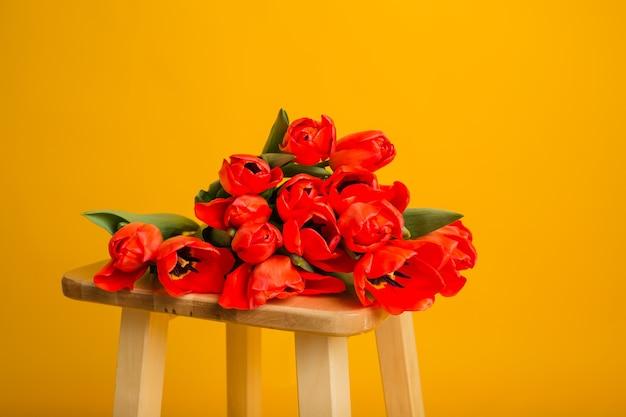 Close de um buquê de tulipas vermelhas em uma parede amarela
