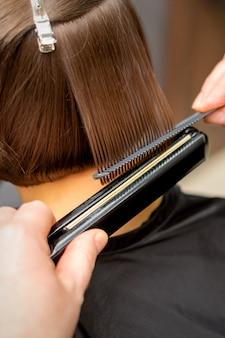 Close de um cabeleireiro alisando o cabelo curto de uma cliente com uma chapinha em um salão de beleza