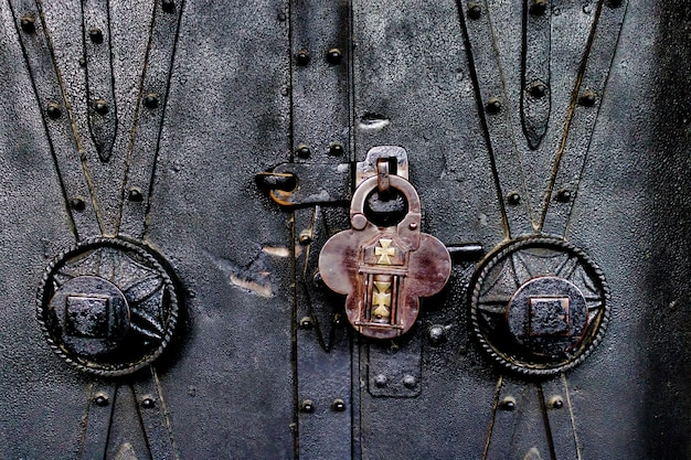 Close de um cadeado antigo na porta de uma igreja ornamentada