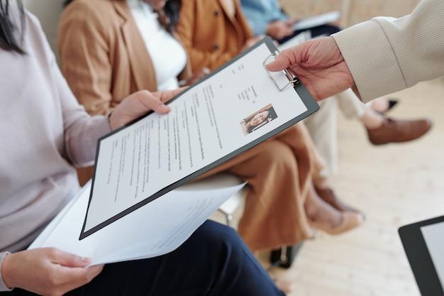 Close de um candidato a emprego irreconhecível passando o currículo para o gerente de recrutamento enquanto está sentado na fila e esperando pela entrevista
