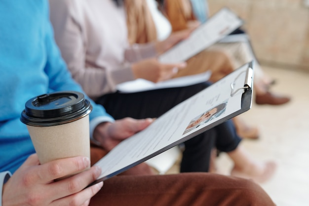 Close de um candidato a emprego irreconhecível segurando um currículo e bebendo café enquanto espera na fila pela entrevista
