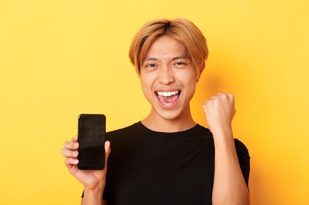Close de um cara asiático feliz, exultante, mostrando a tela do smartphone e dizendo sim, erguer o punho para triunfar, vencer ou alcançar o objetivo, parede amarela
