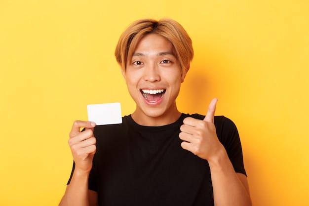 Close de um cara bonito asiático feliz e satisfeito, mostrando o cartão de crédito e o polegar para cima em aprovação, sorrindo surpreso, em pé na parede amarela