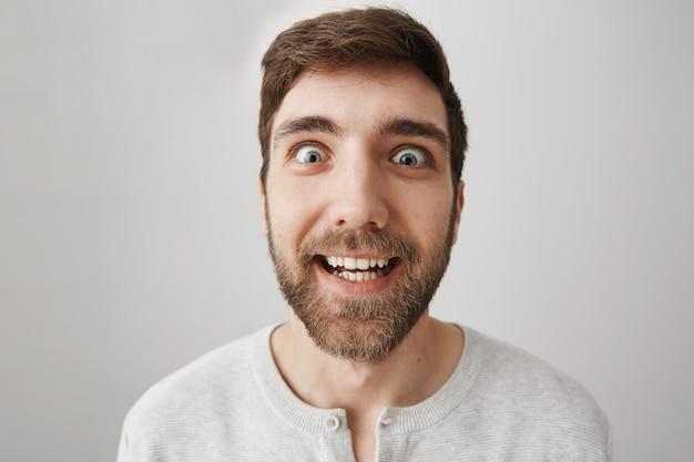 Close de um cara engraçado animado com uma expressão maluca, sorrindo