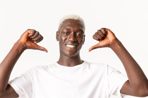 Close de um cara loiro afro-americano bonito e confiante apontando para si mesmo, orgulhoso e assertivo