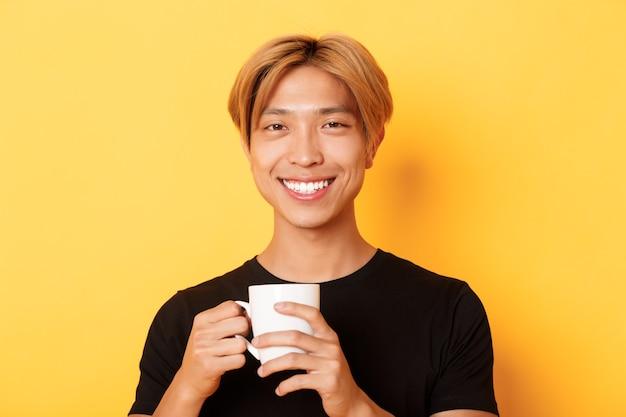 Close de um cara sorridente asiático feliz e satisfeito, segurando uma caneca com café, bebendo e parecendo satisfeito, em pé sobre a parede amarela