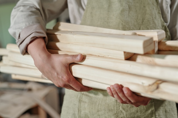 Close de um carpinteiro irreconhecível no avental carregando uma pilha de pranchas de madeira para fazer móveis