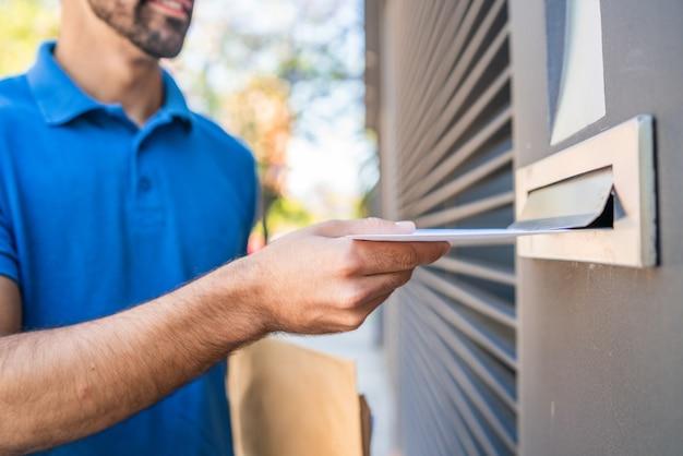 Close de um carteiro colocando uma carta na caixa de correio de uma casa