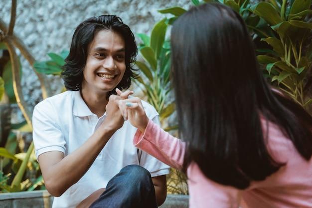 Close de um casal adolescente sentado com movimentos promissores dos dedos enquanto conversa no jardim