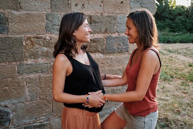 Close de um casal de lésbicas grávidas fazendo uma sessão de fotos em um parque