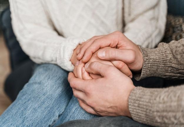 Close de um casal de mãos dadas