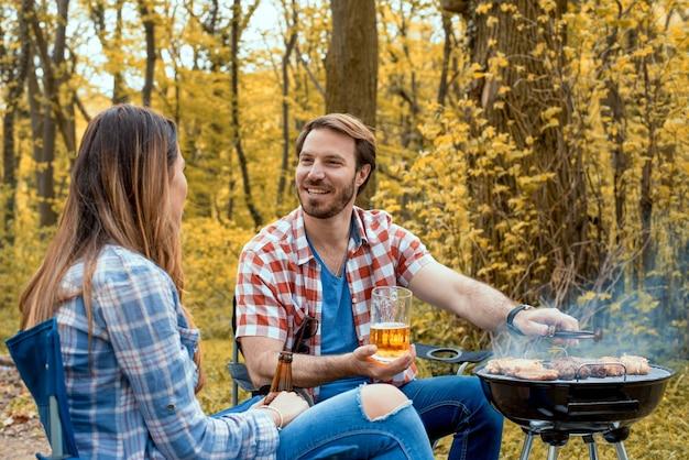 Close de um casal sorridente fazendo churrasco na floresta