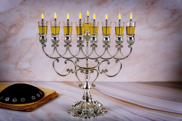 Close de um castiçal aceso de chanucá com velas menorá, um feriado judaico tradicional