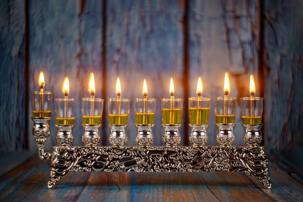 Close de um castiçal de chanucá em chamas com velas menorah