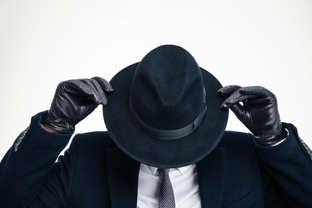 Close de um chapéu preto usado por um homem de negócios de terno preto e seguro por luvas pretas modernas sobre a parede branca