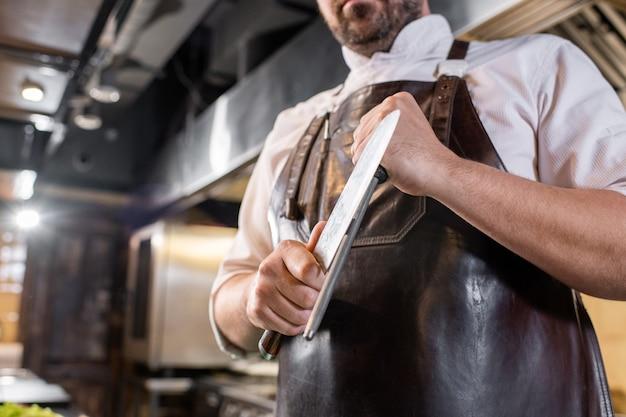 Close de um chef profissional usando uma haste de polimento para afiar uma faca de cozinha no local de trabalho