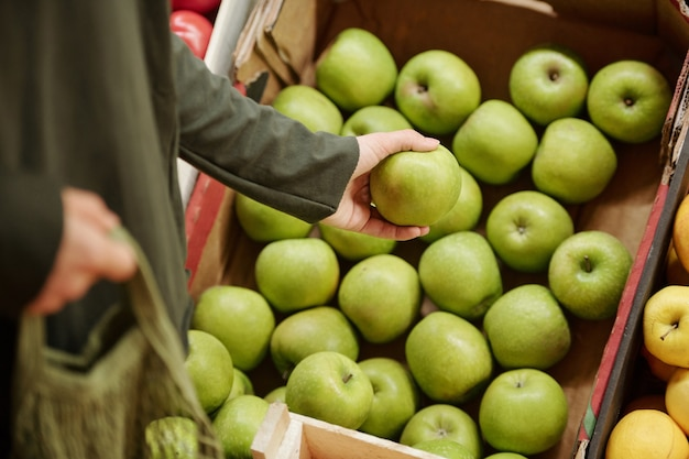 Close de um cliente irreconhecível em pé no balcão e escolhendo maçãs verdes na caixa