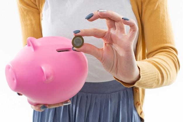 Close de um cofrinho rosa e uma moeda nas mãos de uma menina