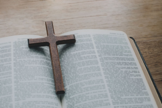 Close de um colar de cruz cristã simples de madeira na bíblia. conceito de esperança, fé, cristianismo
