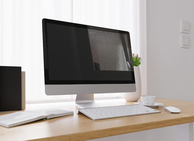 Close de um computador, uma xícara de café, um vaso de flores e muito mais em uma mesa branca