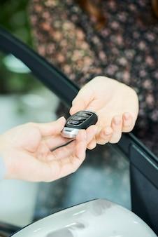 Close de um concessionário entregando a chave do carro novo para o proprietário