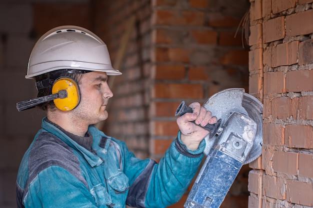 Close de um construtor em um capacete de proteção em uma instalação de trabalho com uma ferramenta de corte.